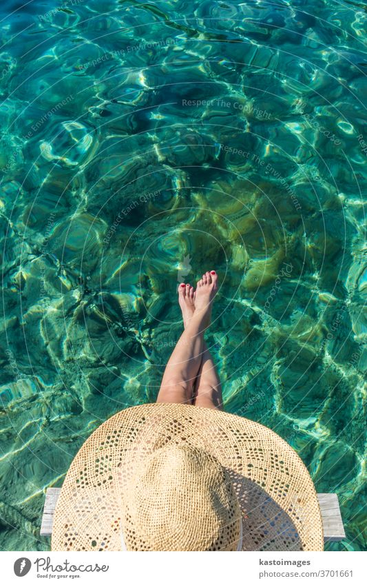 Graphic image of top down view of woman wearing big summer sun hat relaxing on small wooden pier by clear turquoise sea water leisure beauty girl person blue