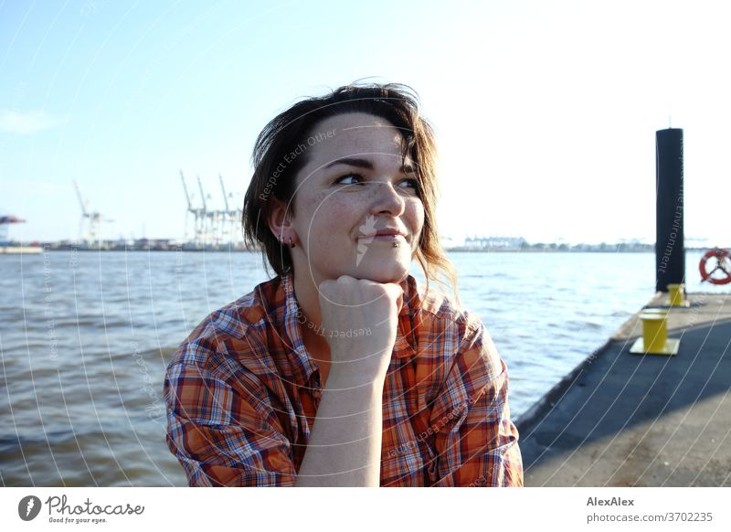 Young woman with freckles sitting on a pontoon in front of Hamburg harbour portrait Central perspective Looking brunette hair Copy Space right freckly Joy Model