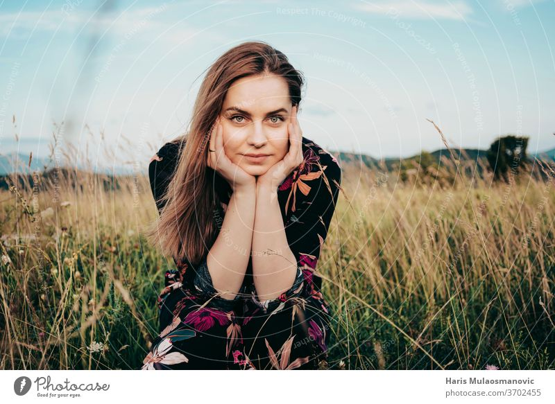 Blonde woman in flower dress looking ate the camera, sitting in the grass field adult beautiful beauty blonde blu sky caucasian face fashion female freedom girl