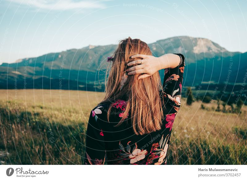 blonde woman looking at the beautiful landscape mountains adult beauty blu sky caucasian dress face fashion female field flower dress freedom girl grass field
