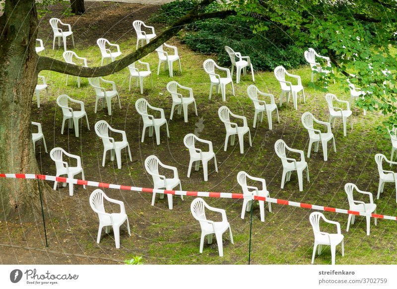 The white plastic chairs had gathered in the park, of course in compliance with the distance rule Park Plastic chairs barrier tape gap Distance rule White Green