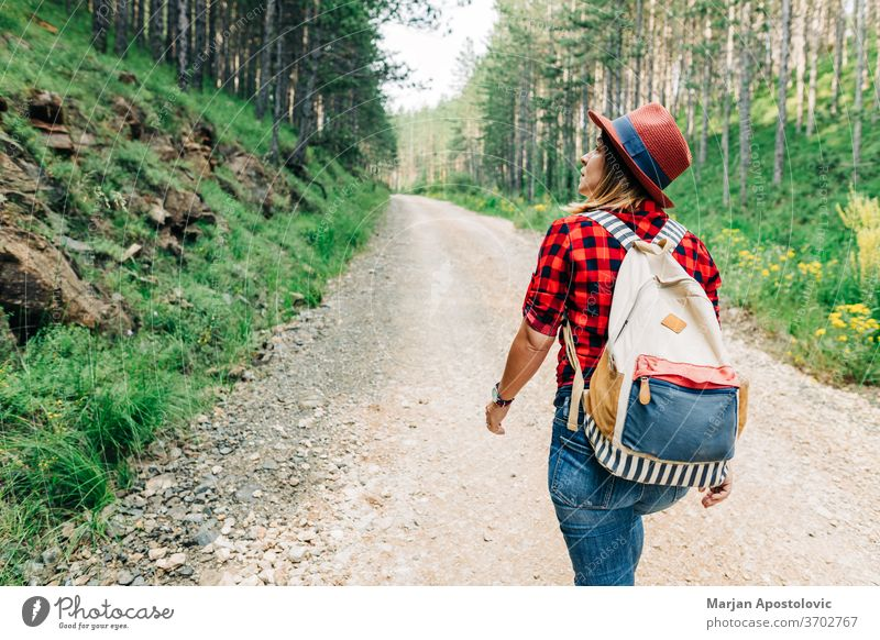 Young female nature explorer walking on mountain dirt road active adventure alone backpack discovery enjoy forest free freedom gravel green healthy hike hiker