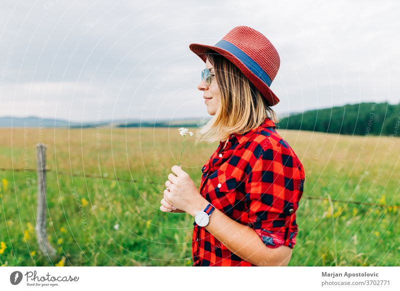 Young woman standing in a meadow with flower in her hands adult beautiful beauty blonde casual caucasian country countryside cute enjoying environment female
