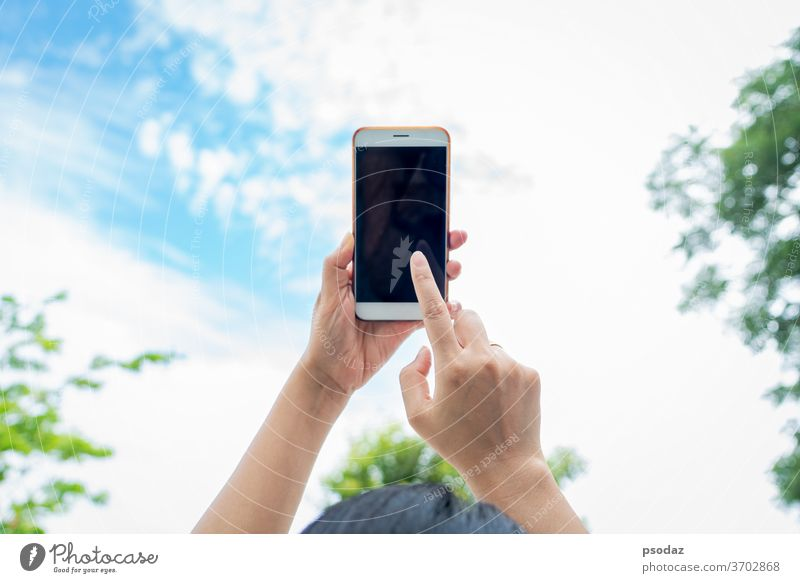 woman holding smartphone with blurred sky background abstract adult blue business call cell communication concept contact design digital filter finger hand