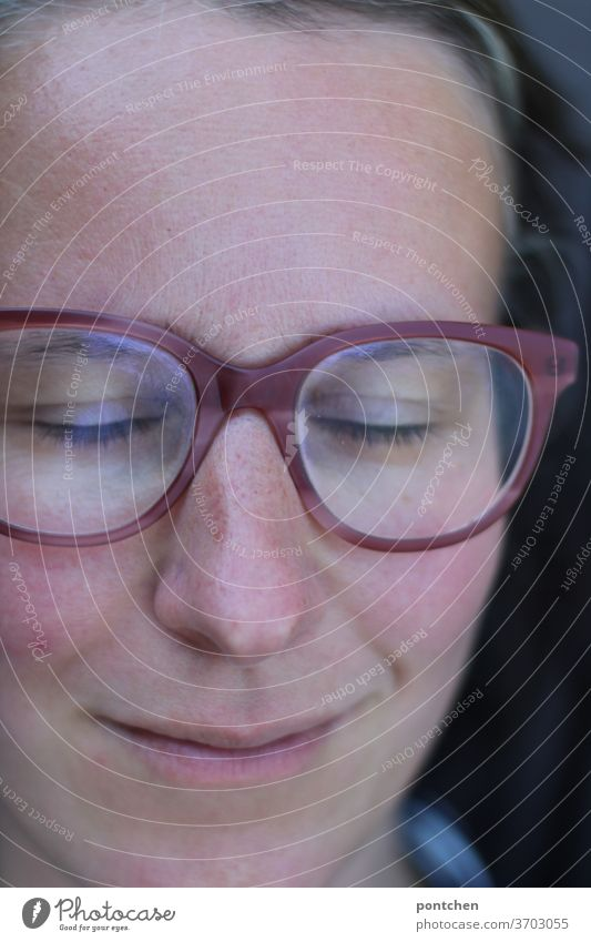 Face of a smiling woman with glasses and closed eyes. Relaxation and satisfaction Woman Eyeglasses smile relaxation Contentment Sleep doze Closed eyes Freckles