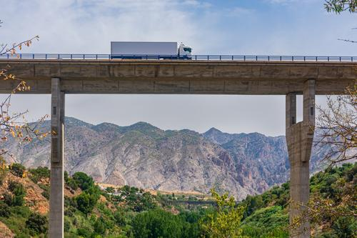 Truck with refrigerated semi-trailer crossing a viaduct with a landscape of mountains in the background truck bridge road trayler transportation highway travel