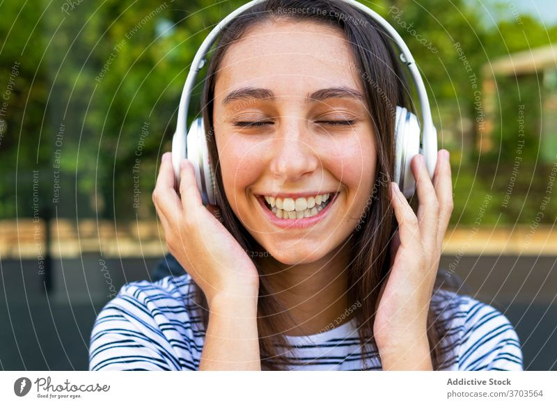 Calm woman listening to music in city headphones enjoy song carefree dreamy satisfied female glass wall building mirror reflection wireless relax happy gadget