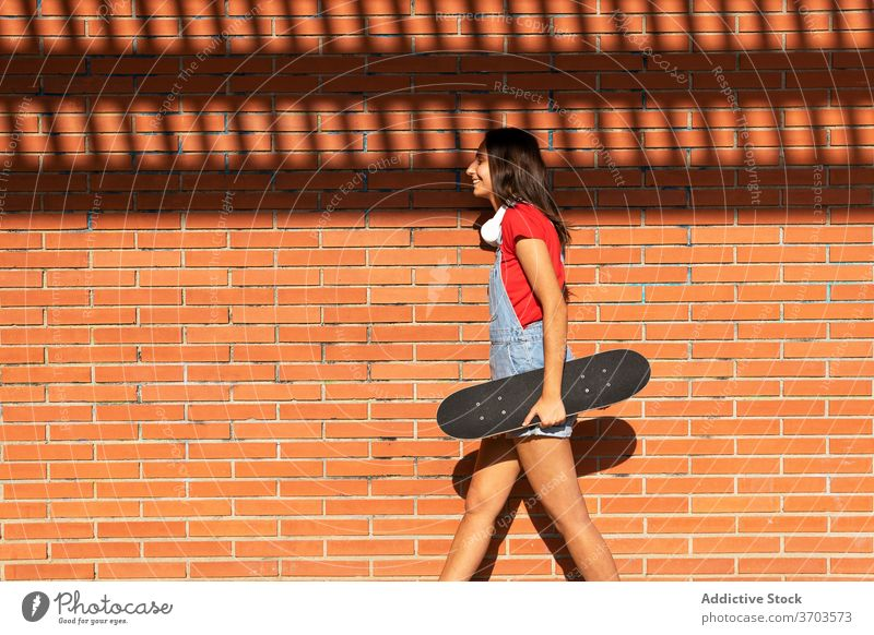 Cheerful woman with skateboard in city millennial having fun skater cheerful laugh funny female urban generation young joy smile trendy carefree cool enjoy