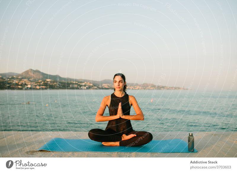 Flexible woman meditating in Lotus pose meditate lotus pose yoga sunset sea mindfulness mat harmony relax female seascape asana tranquil healthy padmasana mudra