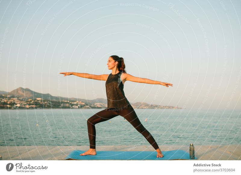 Calm woman in Warrior pose on yoga mat warrior pose virabhadrasana calm practice sea barefoot sportswear female tranquil amazing seascape wellness slim idyllic