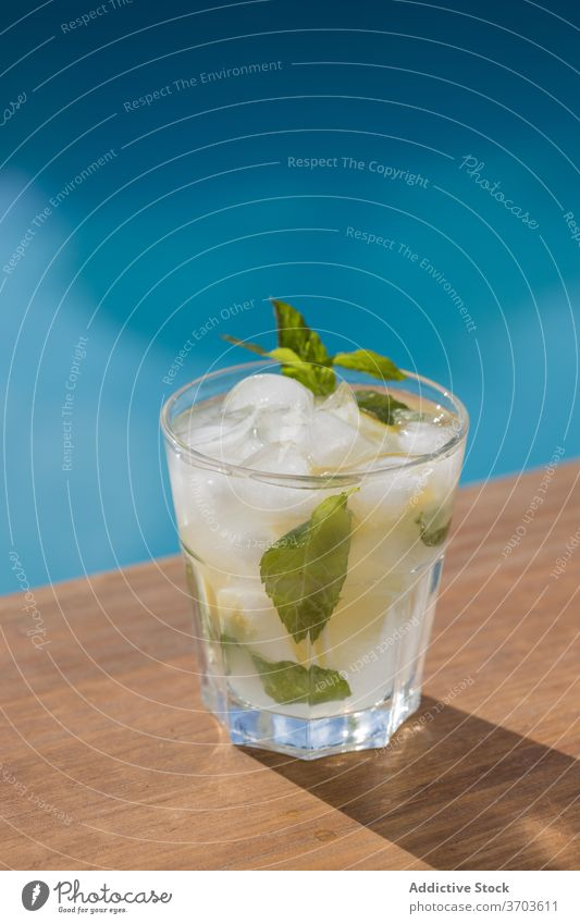 Glass of Mojito cocktail near swimming pool mojito drink alcohol ice lemon mint glass cold beverage citrus refreshment fruit cool tasty delicious gourmet serve