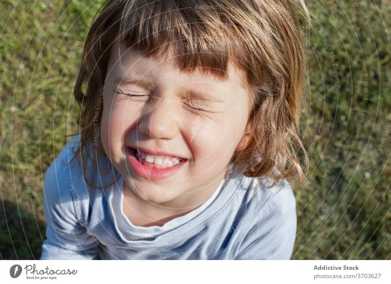 Cute little child in field make face grimace cheerful weekend funny kid summer having fun cute joy happy rest grass adorable relax sit childhood playful sweet