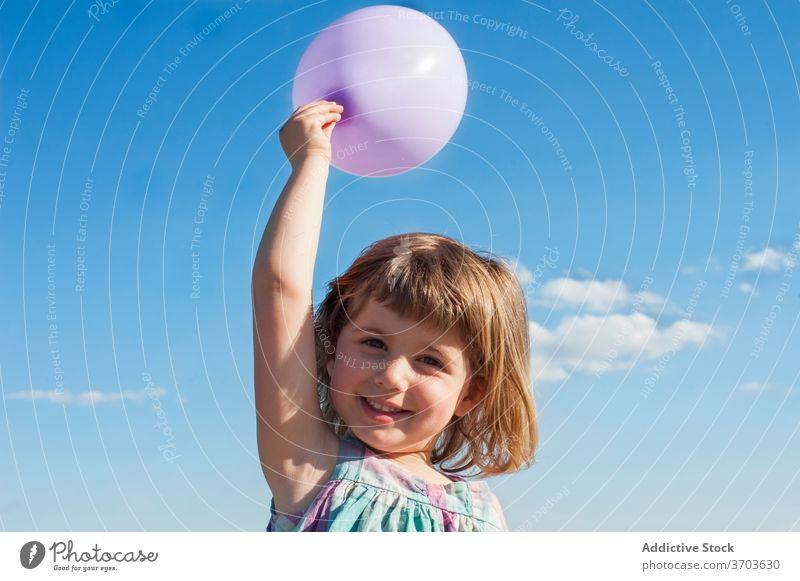 Content girl with balloon in summer child having fun kid toy air balloon joy childhood smile dress cheerful holiday summertime blue sky sunshine bright adorable