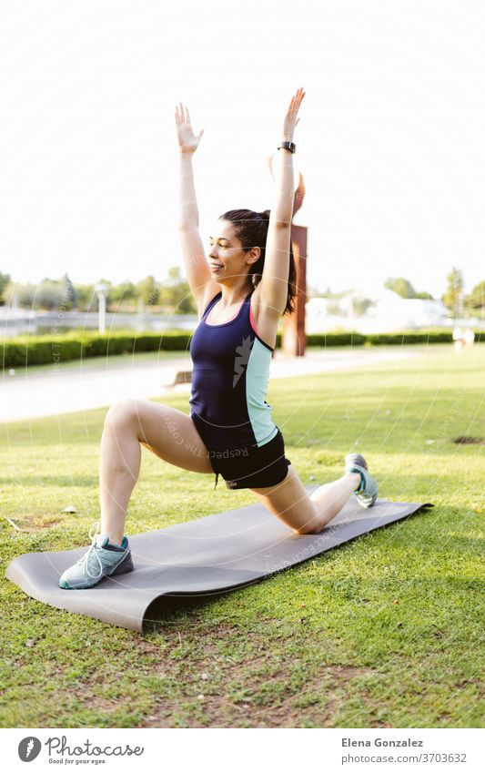 Young brunette woman in the park exercising and stretching on a mat fit yoga fitness exercise meditation sports balance pose relaxation workout