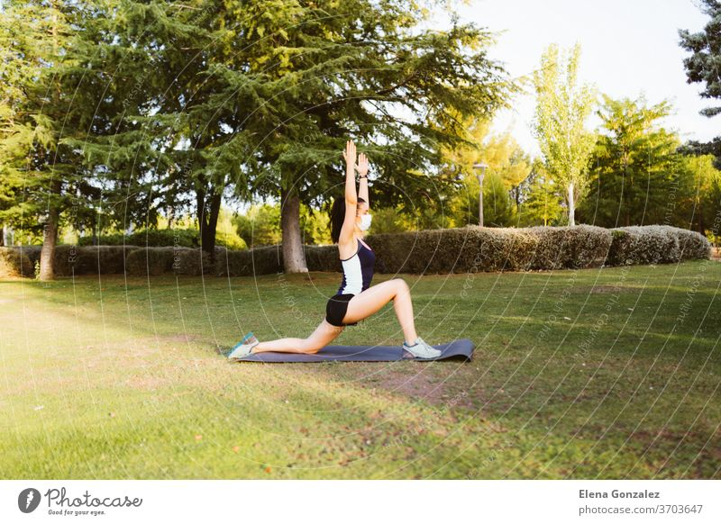 Young brunette woman with a mask exercising and stretching on a mat in the park fit yoga pandemic covid fitness exercise meditation coronavirus sports balance