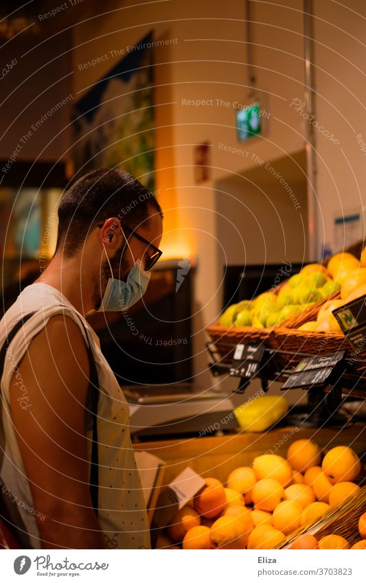 Man wearing a face mask/mouthpiece while shopping in the supermarket during the Corona pandemic. Shopping Mask Supermarket fruit Mask obligation shank