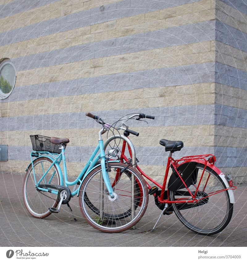 short rest - two bicycles stand on a sidewalk in the city in front of a wall Bicycle Vehicle Means of transport Cycling Leisure and hobbies Exterior shot