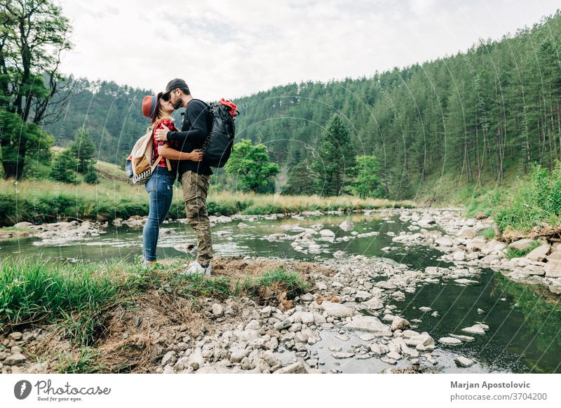 Young couple nature explorers kissing by the river in the mountains adult adventure backpack backpacker casual creek expedition exploration forest happy hike