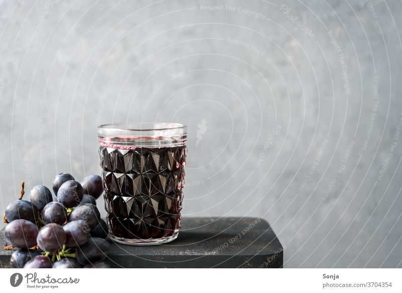 Fresh grape juice in a glass and blue grapes on a grey background Grape juice Glass Bunch of grapes Blue Beverage fruit Alcoholic drinks Vine Red wine Food