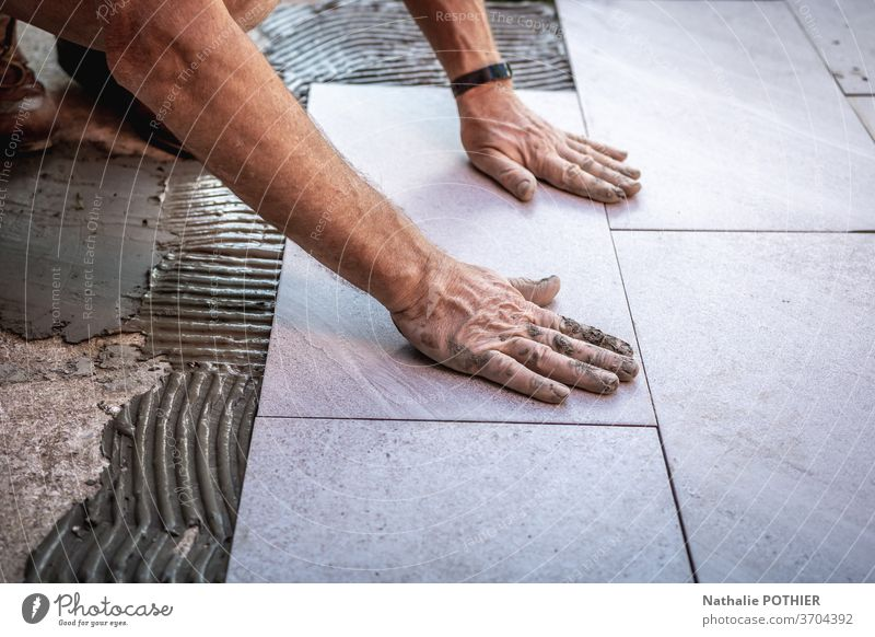 Tile installation with glue on concrete floor tile adhesive renovation profession worker working flooring decoration material tiling pose renewal construction