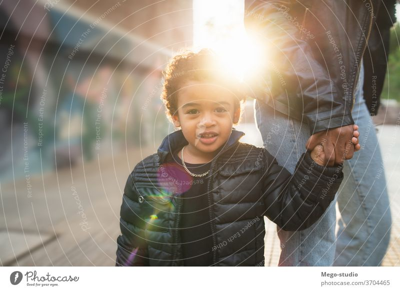 African american boy holding mother's hand. black child happy outdoors people caucasian person african american mixed race fun enjoyment day childhood children