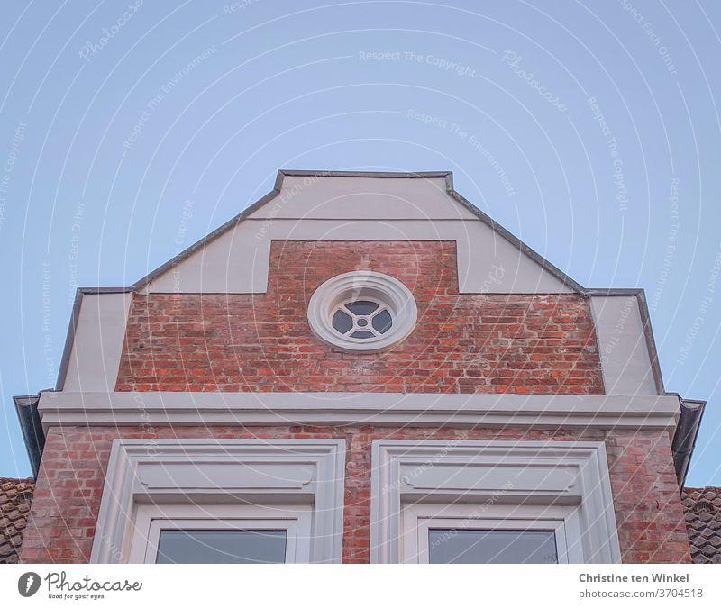 House gable / relay gable with red clinker bricks, white plaster and a round pretty window in front of a light blue sky house gables Gable pediment