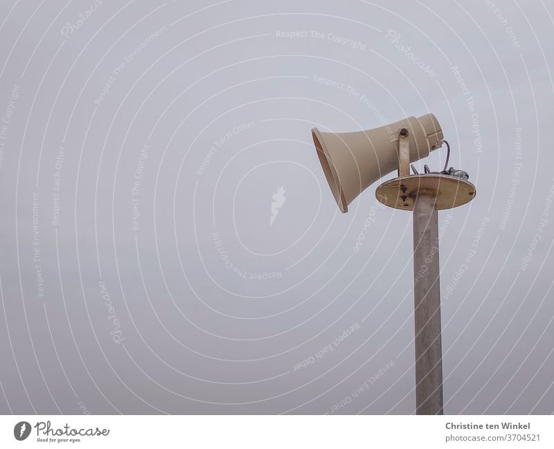 Side view of an older loudspeaker in the shape of a megaphone in front of a hazy sky Loudspeaker Megaphone Pole Sky Communicate announcement Information