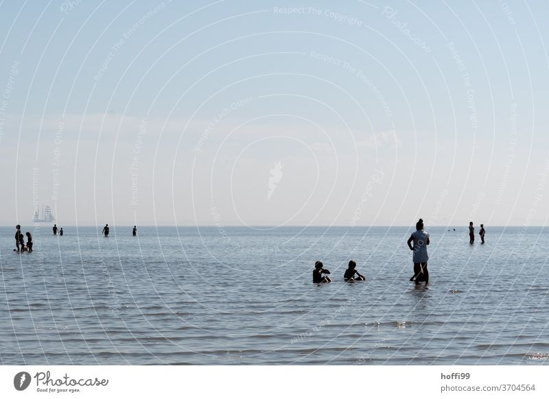 people refresh themselves in the rising tide - summer freshness at the sea fresh from the summer Mud flats High tide bathe shallow water accruing water