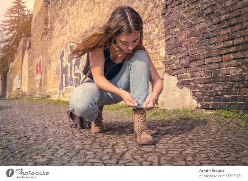 young woman in summer clothes ties her shoes crouching street outdoor beautiful concentrated bag wall brick Berlin lifestyle pavement teen teenager girl casual