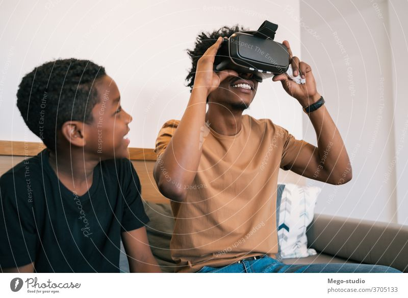 Father and son playing with VR glasses. father game video together african american relaxing adorable electronic relationship video game technology device hobby