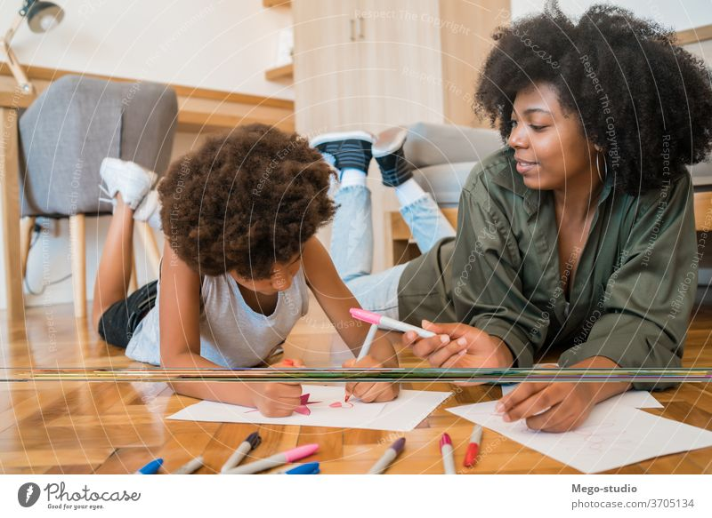 Mother and son drawing with colored pencils on floor. fun mother home together mom black people african american mixed race family kids leisure floor fun indoor