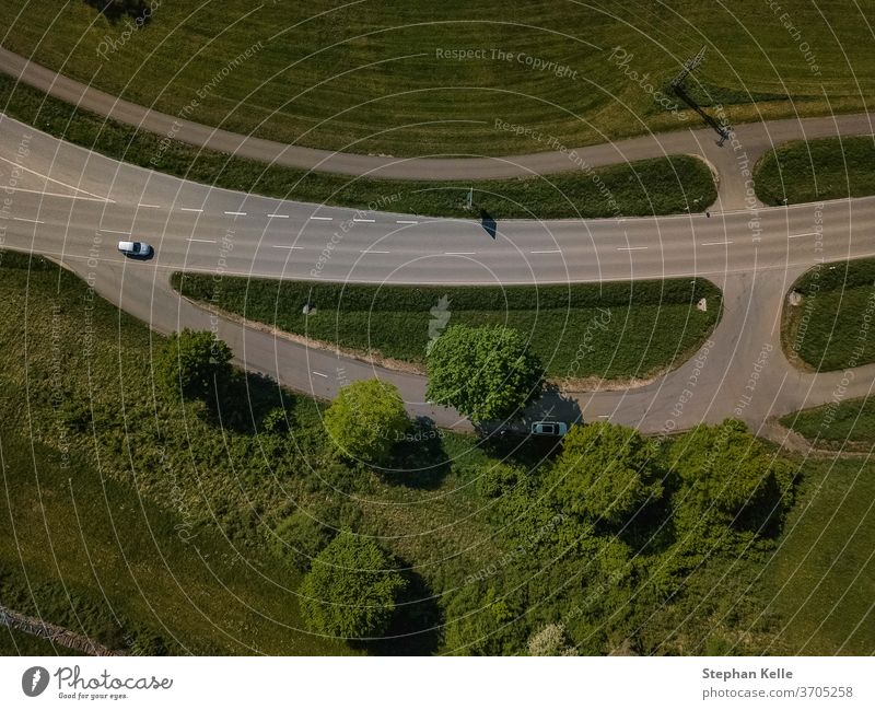 The top view of a car at a country road made by a drone. Car vertical street from above traffic parking slot asphalt up in the sky trees day birds eye view