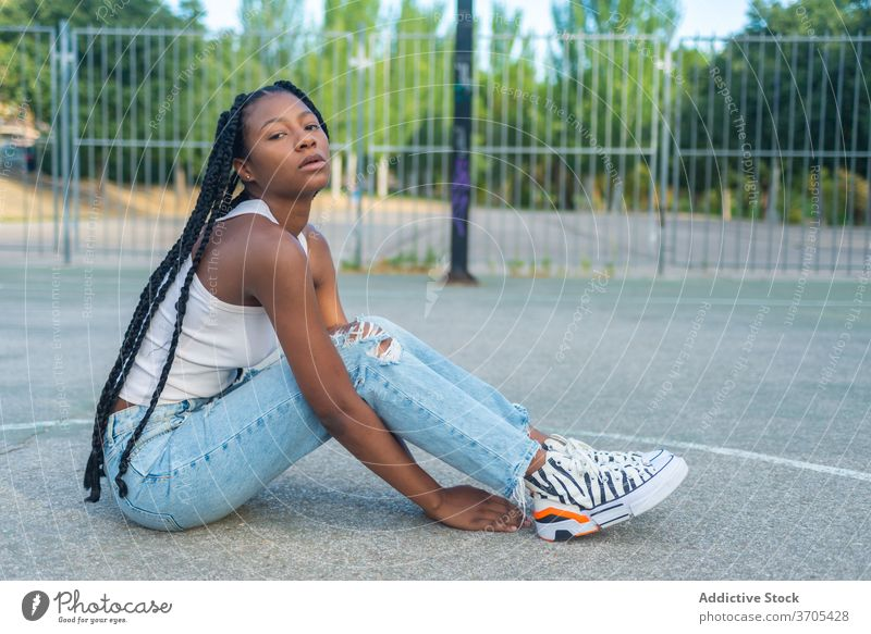 Young black woman sitting on sports ground urban style street style trendy hipster young braid ethnic millennial female jeans basketball outfit fashion casual