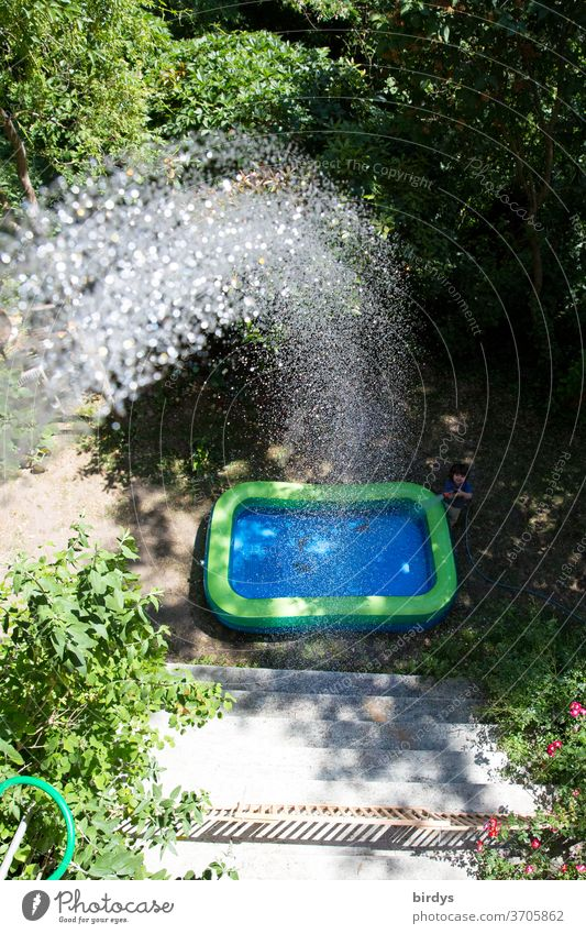 A paddling pool in the garden which is filled from the balcony.  Water jet Paddling pool Jet of water Summer ardor cooling Drops of water Refreshment Sunlight