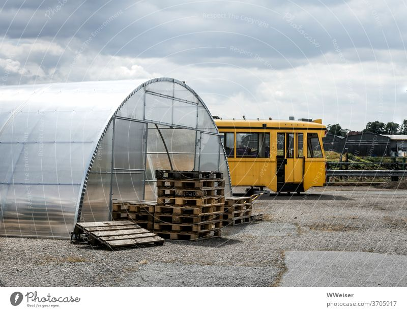 Glass house, pallets and parked tram in Bremen-Überseestadt Tram Palett glass house Greenhouse Empty turned off European port Weser overseas city Territory