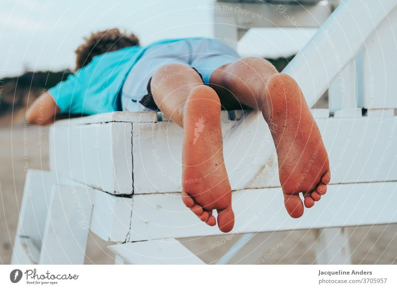 Boy lies barefoot on a chair on the beach Boy (child) Child Beach Legs feet Summer Barefoot Sand Exterior shot Toes Vacation & Travel Ocean Relaxation