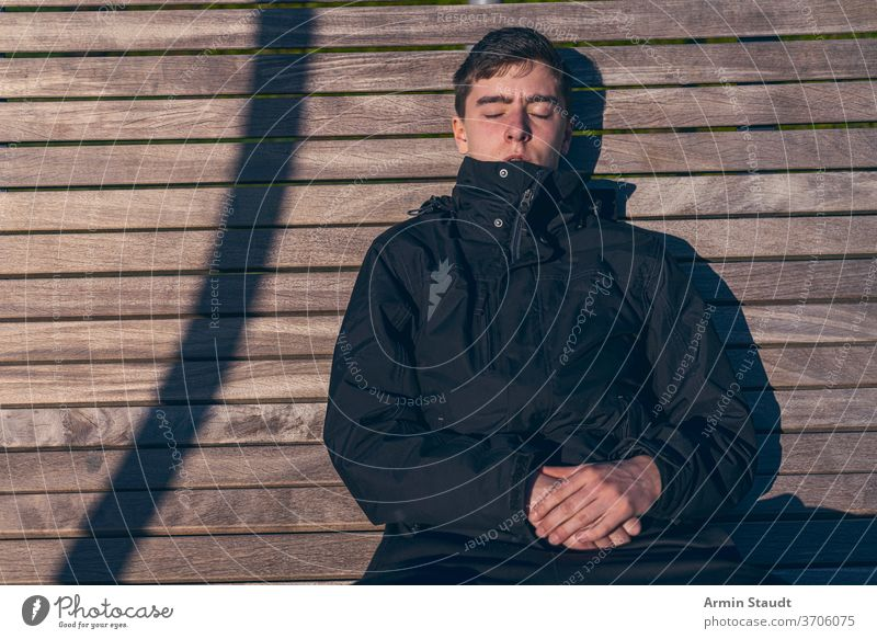 Young man sitting on a bench in the sun with his eyes closed young sunbath sunlight outdoors sleep relax leisure hands silent shadow wood portrait teenager