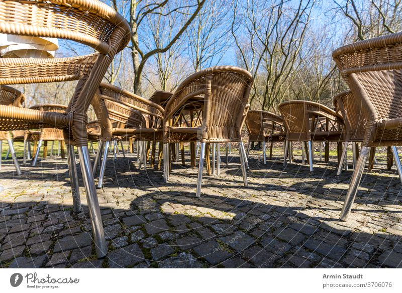 empty wicker chairs of a cafe on the terrace, outside table furniture restaurant nobody outdoor seat street leisure outdoors armchair rattan cobblestone trees
