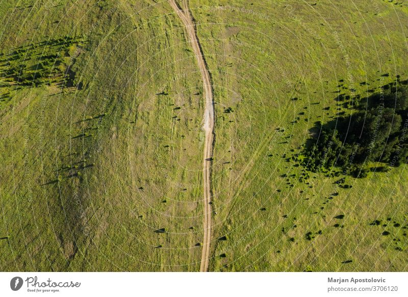 Aerial view of a dirt road going through mountain planes above adventure aerial agriculture background beautiful beauty countryside drone ecology environment