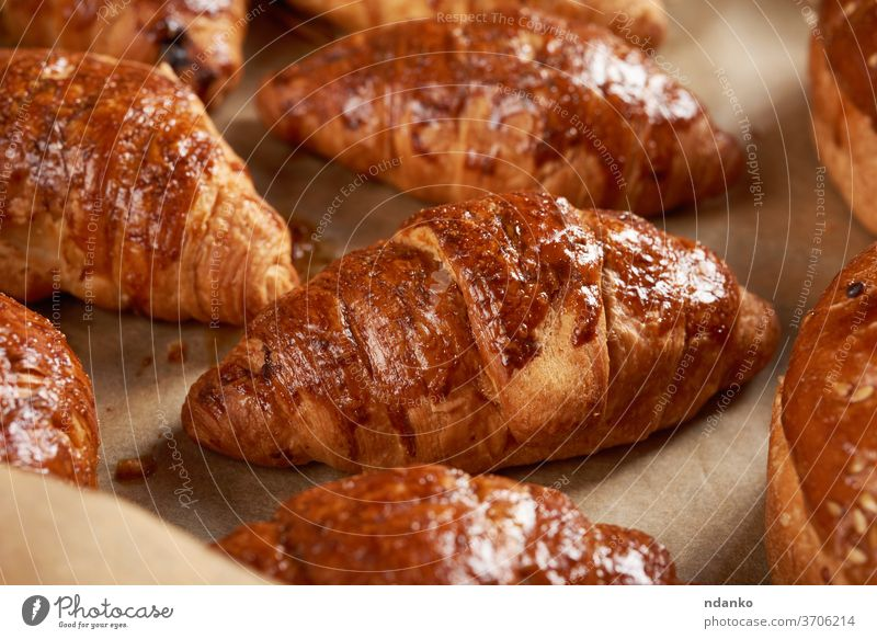baked croissants in a baking sheet on brown parchment paper, delicious and appetizing pastries crispy crust cuisine bakery bread breakfast bun closeup dessert
