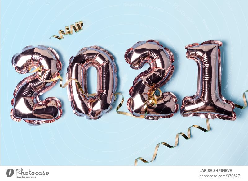 Gold pink balloons in form of numbers 2021 whis golden serpentine on blue background. Happy New Year celebration. Flat lay, top view eve party foil parkle