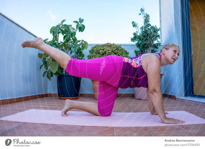 Exercise at home. Middle-aged woman in poor shape exercising on a mat on the terrace of her house person body active sunset urban activity portrait flexibility