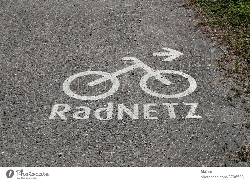 Bicycle path markings on the asphalt. German text: Bike network bike lane road sign symbol urban way background bicycle city direction track traffic transport