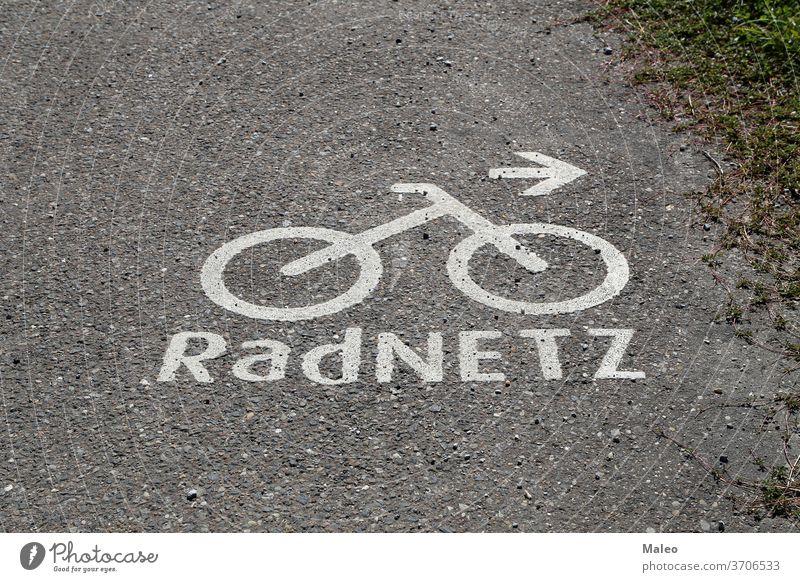 Bicycle path markings on the asphalt. German text: Bike network bike lane road sign symbol urban way background bicycle city direction track traffic transport