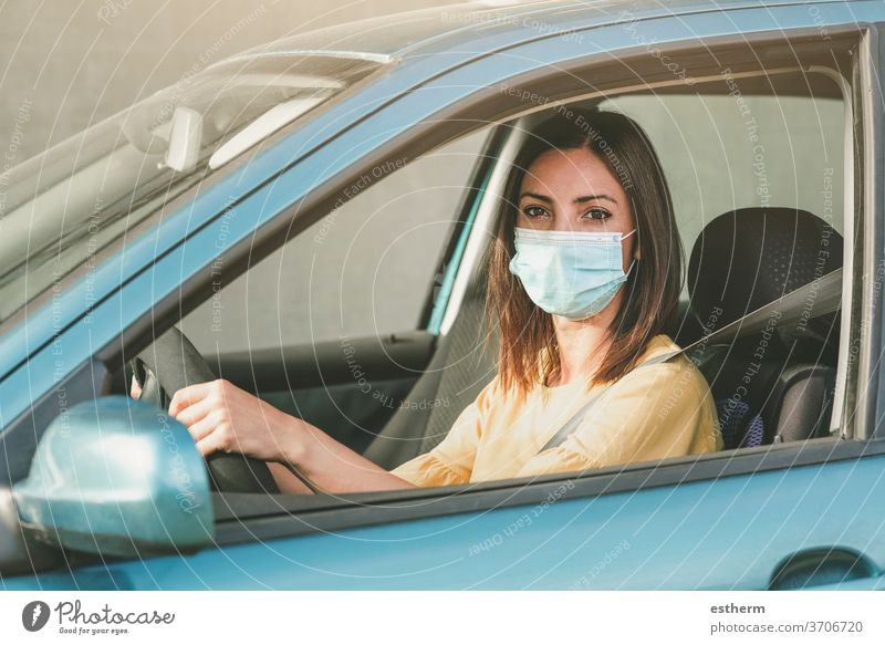 Young woman driving car with medical mask on her face coronavirus young woman covid-19 drive security trip travel destination vehicle people driver outdoors