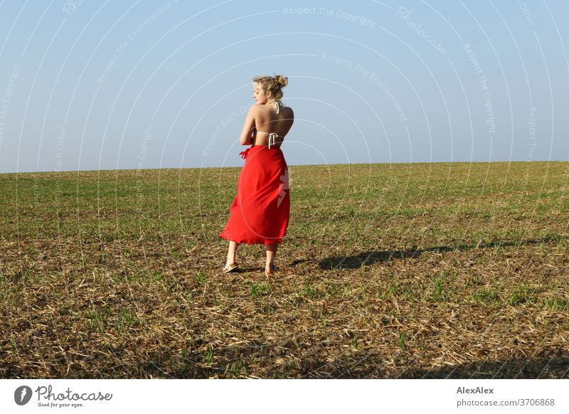 Portrait in back view of a young woman with bikini top and red skirt on a field Light Athletic Feminine Emotions emotionally portrait Central perspective