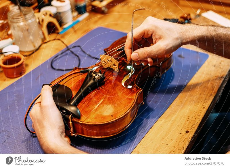 Anonymous luthier installing sound post to violin insert make instrument artisan craft tool hand work setting workshop equipment cello skill master maker
