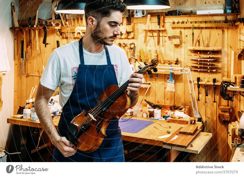 Male master in workshop with violins man repairman instrument music craftsman workbench apron male shiny equipment modern hobby tool focus table professional