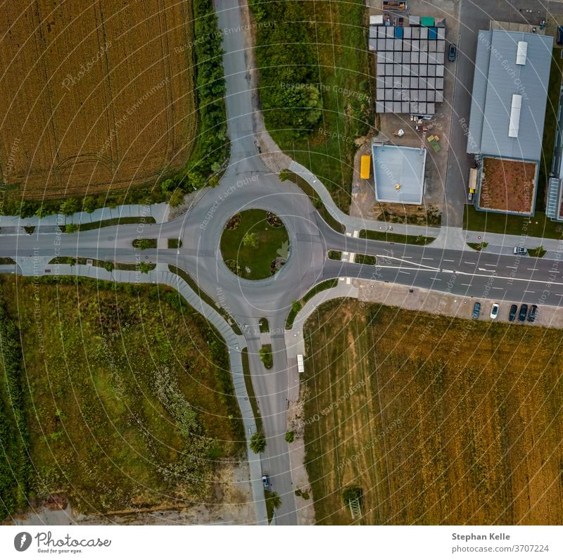 Top down aerial view of a traffic roundabout on a main road in germany. high street background transport path summer transportation drive urban route asphalt