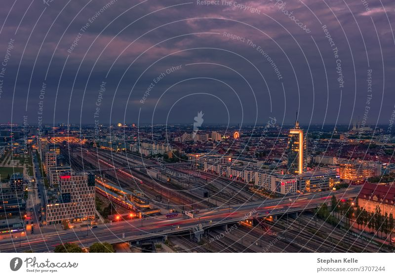 View over Munich at rush hour at the Donnersberger bridge with lights of cars in high angle view. german office tower violett sky street evening trails jam